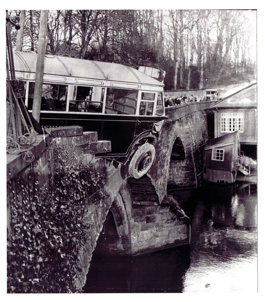 Black and white photo showing a bus that has crashed on a bridge with the front right wheel hanging over the edge. Beyond the bus a line of people, presumably the passengers stand along the bridge.