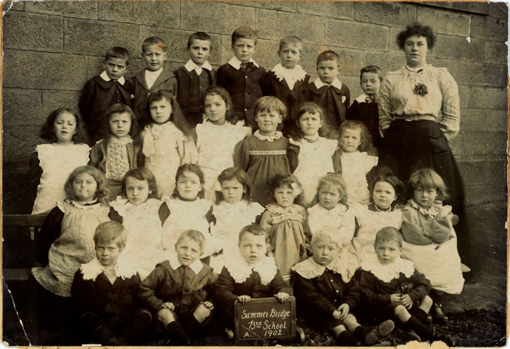 Black and white group photograph showing 27 pupils in the Infants class with their teacher